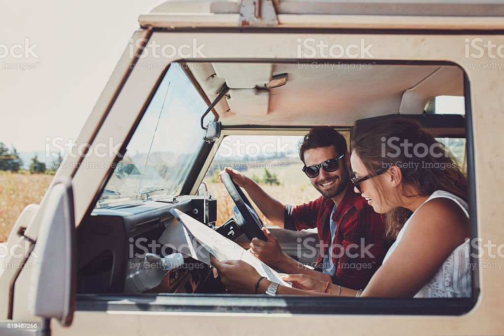 Couple looking at the map in their car stock photo