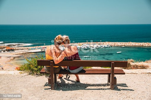 Mature female couple sitting down outside overlooking the sea in Paphos, Cyprus. They are spending quality time together and looking at the view.