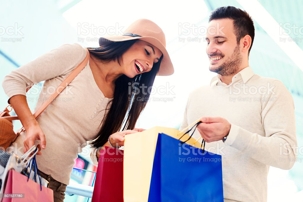 Couple looking at their shopping bags stock photo