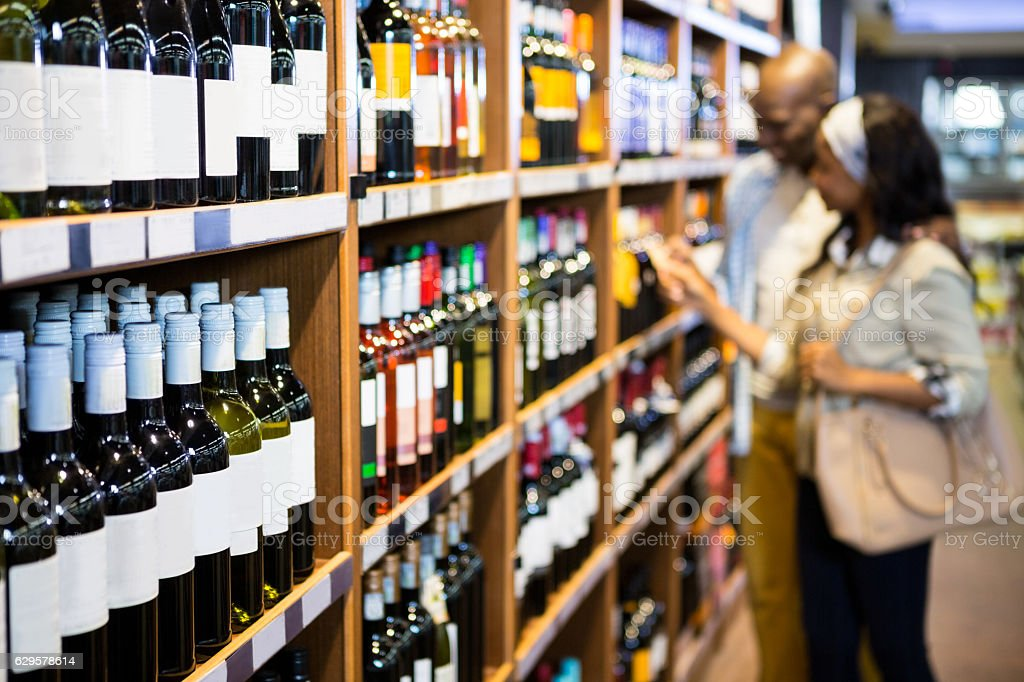 Couple looking at wine bottle in grocery section - foto de acervo