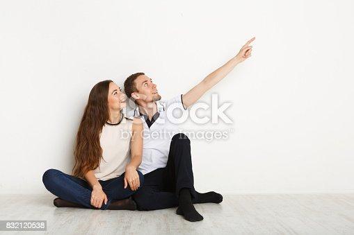 istock Couple looking away, sitting on floor 832120538
