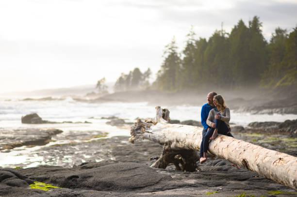 Ehepaar schaut weg, während man sich auf dem gefallenen Baum entspannt – Foto