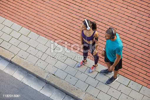 High angle view of couple standing on sidewalk. Man and woman are in sports clothing. They are looking away at city.