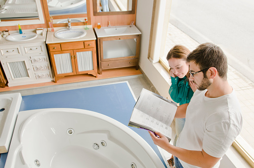 Couple Looking Catalog In Bath Store Stock Photo - Download Image Now