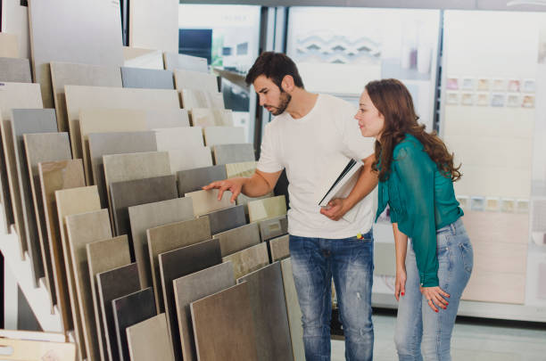 Couple looking ceramic and tiles for their new home floor Couple looking ceramic and tiles for their new home floor. They are choosing in furnitures store ceramics stock pictures, royalty-free photos & images