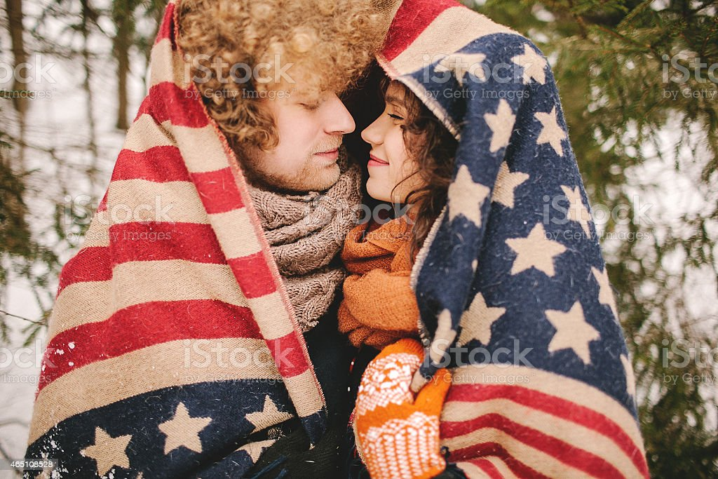Couple looking each other under stars and stripes rug outdoor stock photo