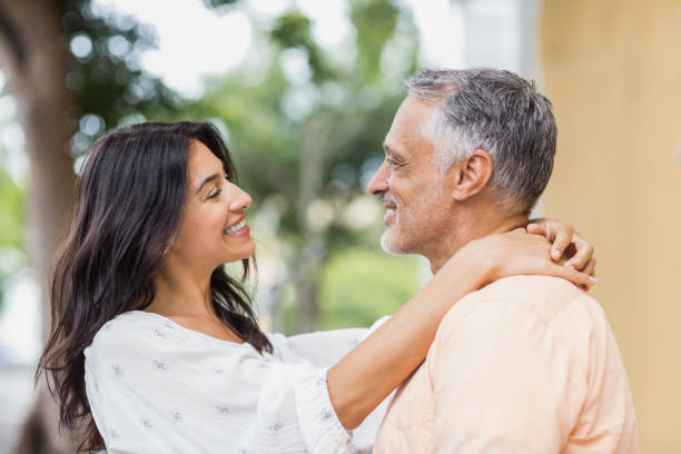 Couple looking each other while embracing stock photo