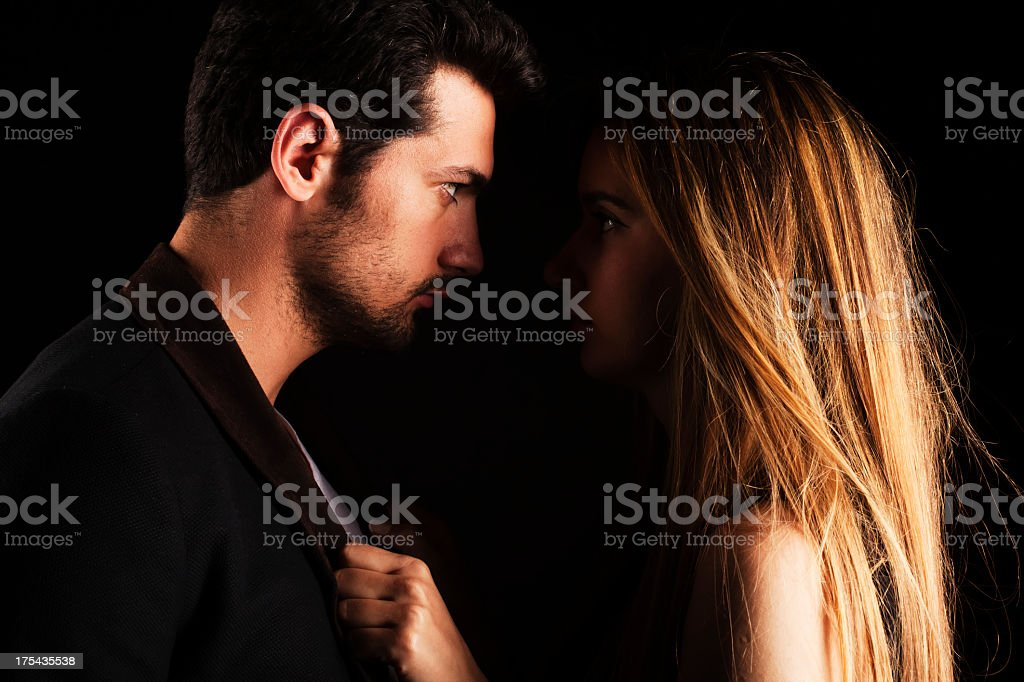 Couple looking fiercely into each other's eyes stock photo