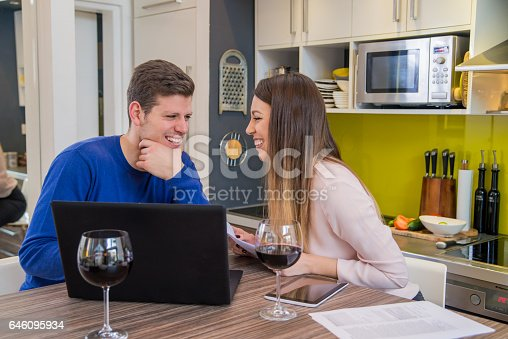 833210686 istock photo couple looking financial documents in laptop  in home interior. 646095934