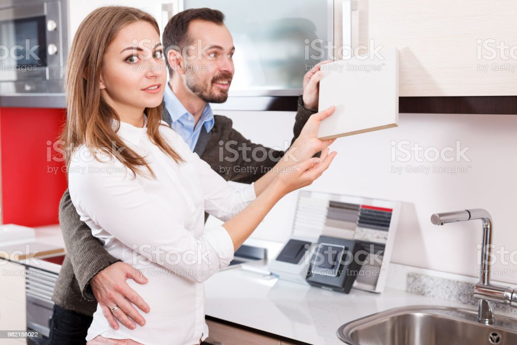 Couple looking for materials for kitchen furnishing stock photo
