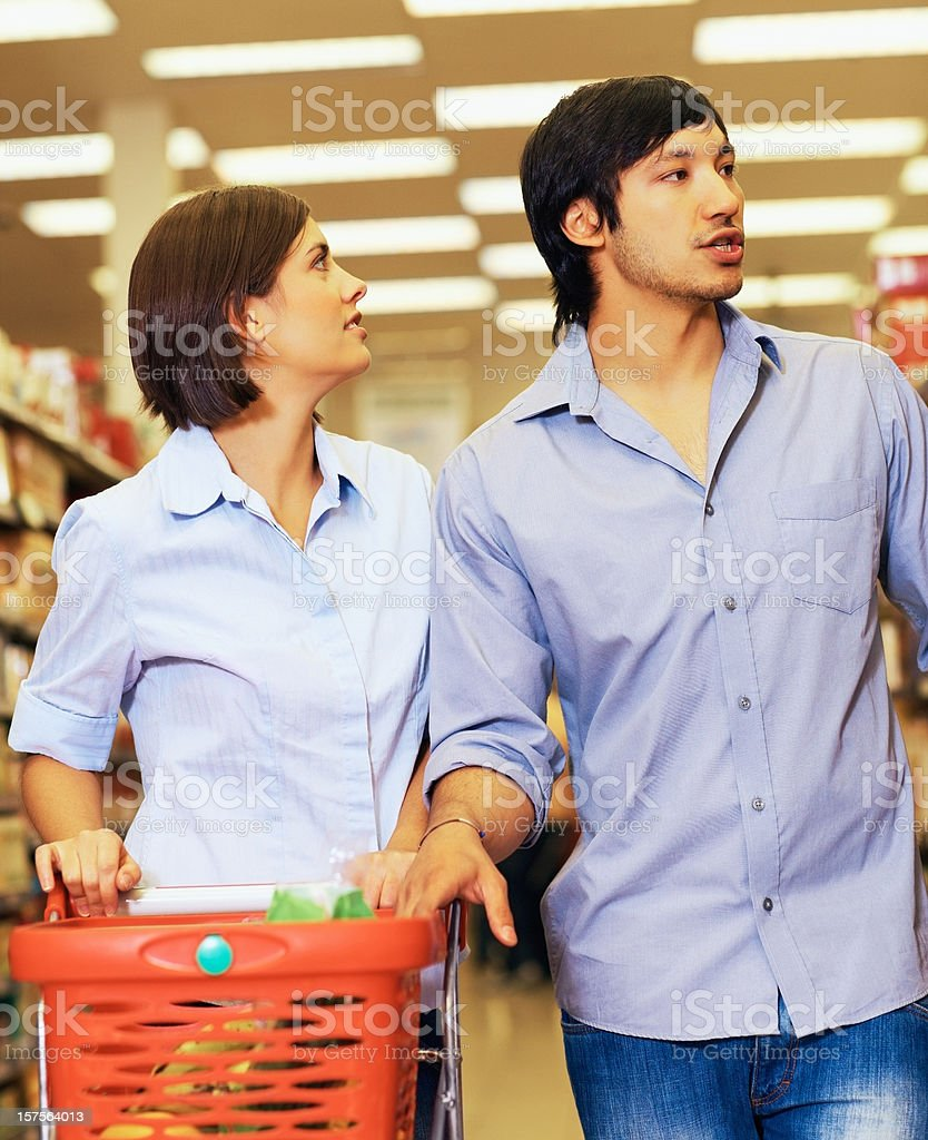 Couple looking for some product at the supermarket royalty-free stock photo