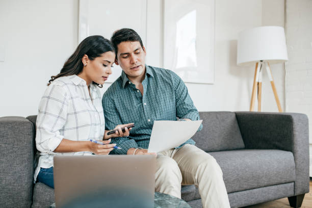 Couple looking on bank statements Couple looking on bank statements cheap stock pictures, royalty-free photos & images