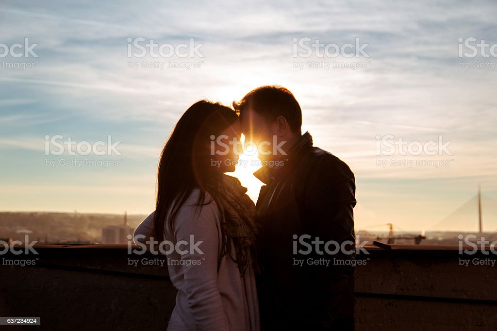 Couple looking on the rooftop at the sunset - foto de acervo