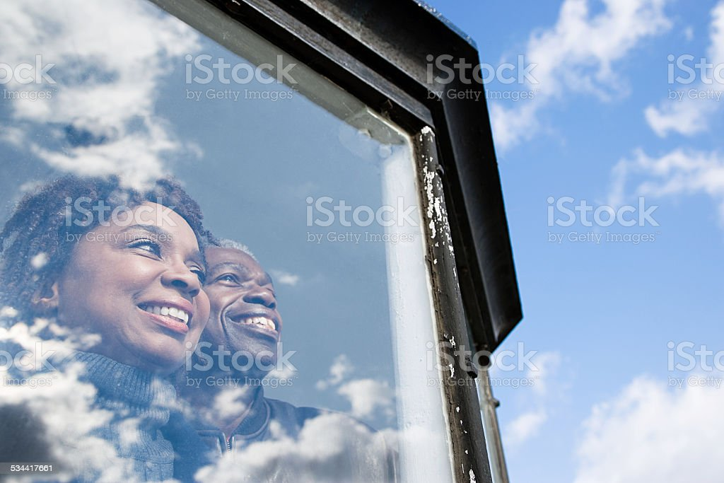 Couple looking out of a window stock photo