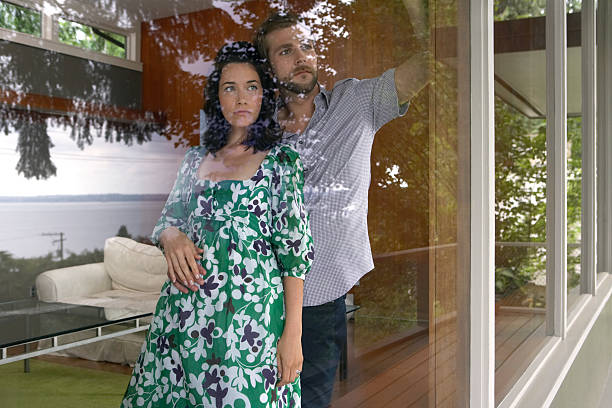 Couple looking out of living room window stock photo