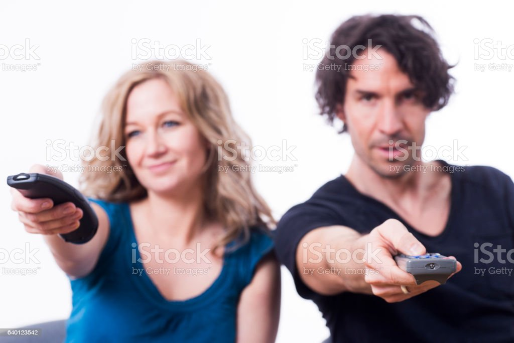 Couple looking television zapping with two remote controls stock photo