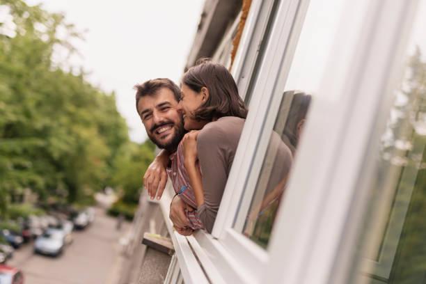 Couple looking through window stock photo
