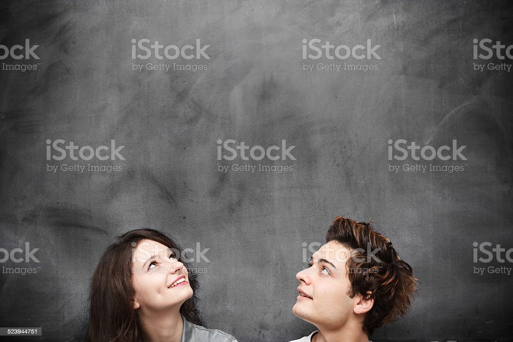 Couple looking up on blackboard background stock photo