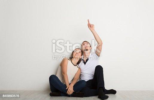 istock Couple looking up, sitting on floor 845860576