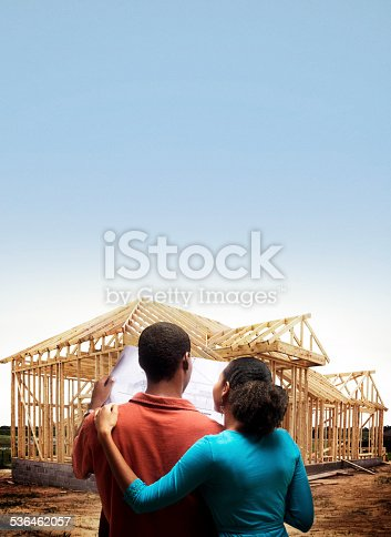African American couple in front of home for sale.