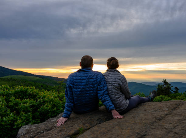 Couple Looks Out Over Sunset Falling on Blue Ridge stock photo