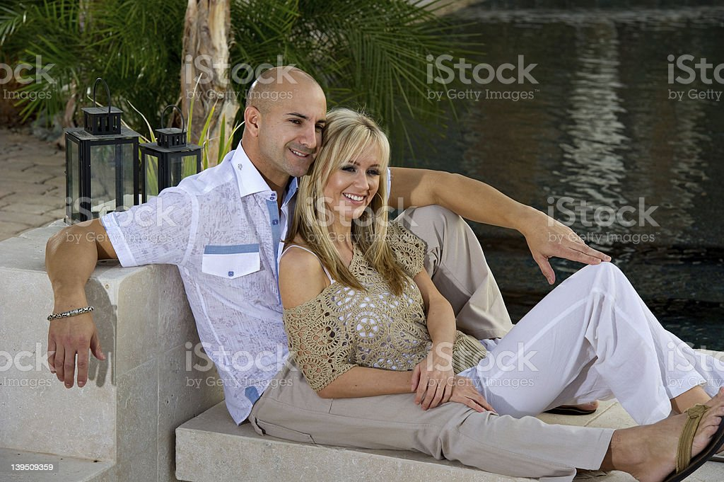 Couple lounging by the pool stock photo
