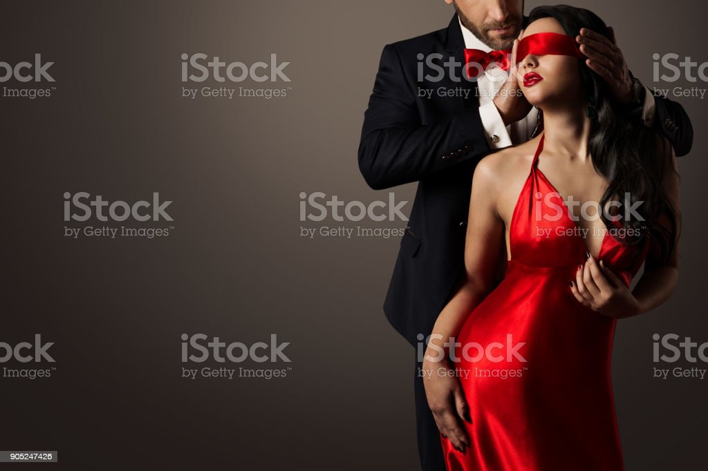 Couple Love Kiss, Sexy Blindfolded Woman Dancing in Red Dress, Elegant Man in Suit stock photo