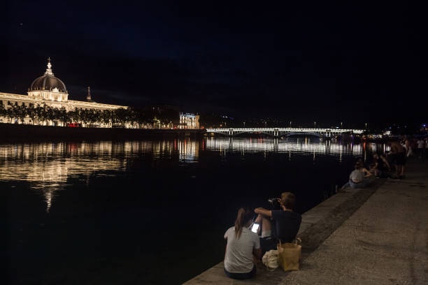 Couple, lovers, looking at a smartphone and taking pictures on the riverbank of the rhone, on the Quais De Rhone, facing Hotel Dieu, one of the main monuments of the city Picture of the Hotel Dieu at night with lovers looking at a smartphone and taking pictures in front. Hotel-Dieu de Lyon was a hospital of historical significance situated on the west bank of the Rhone river transformed into a luxury hotel main de dieu stock pictures, royalty-free photos & images
