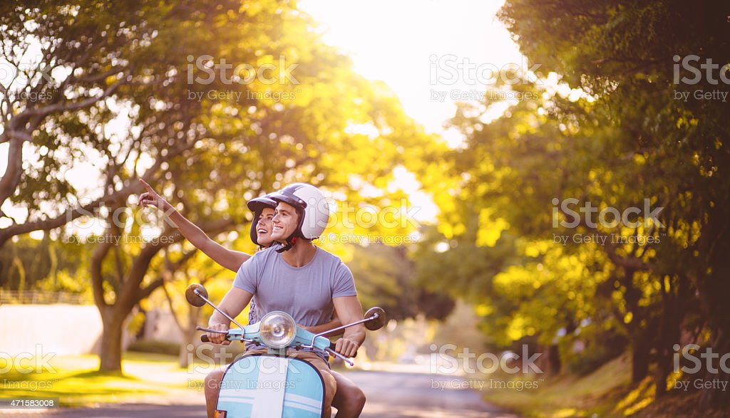 Couple loving the sights on a scooter road trip stock photo