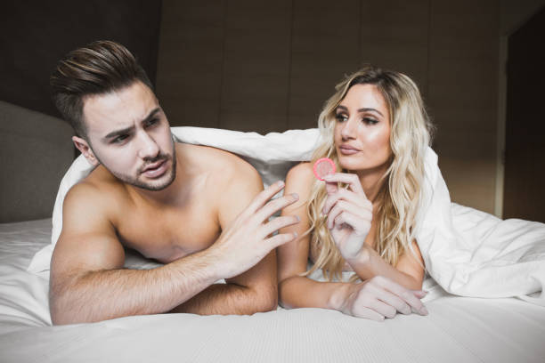 Couple lying in bed while girlfriend is holding a condom stock photo