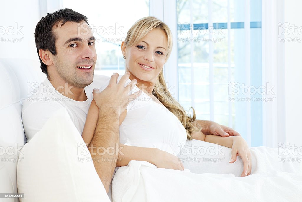 Couple lying in the bed and looking at camera. royalty-free stock photo