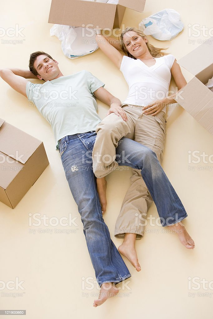 Couple lying on floor by open boxes in new home