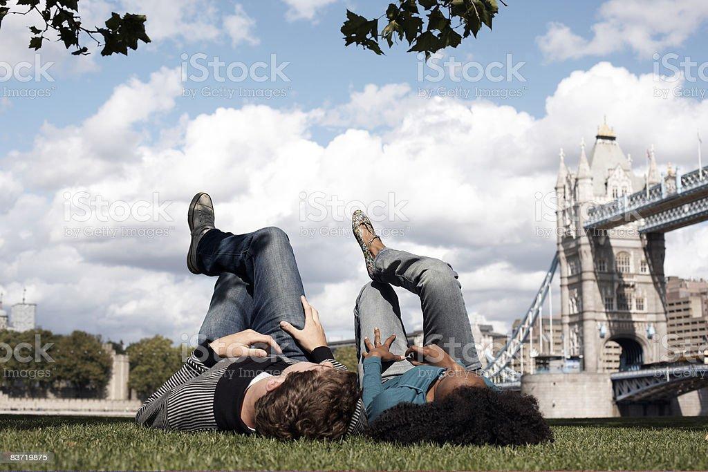 Para leżąc na trawie z widokiem na Tower Bridge zbiór zdjęć royalty-free