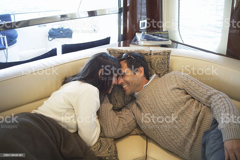 Couple lying on seats on yacht, heads together, smiling  40-44 Years Stock Photo