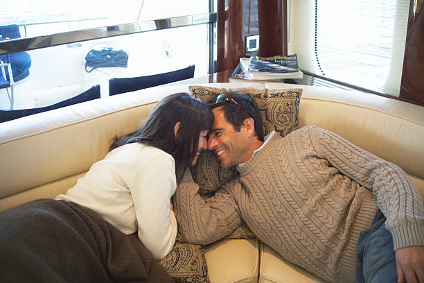 Couple lying on seats on yacht, heads together, smiling stock photo