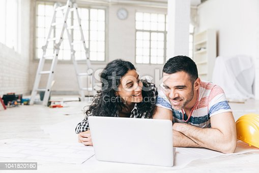 Couple lying on the floor in a new apartment and using a laptop