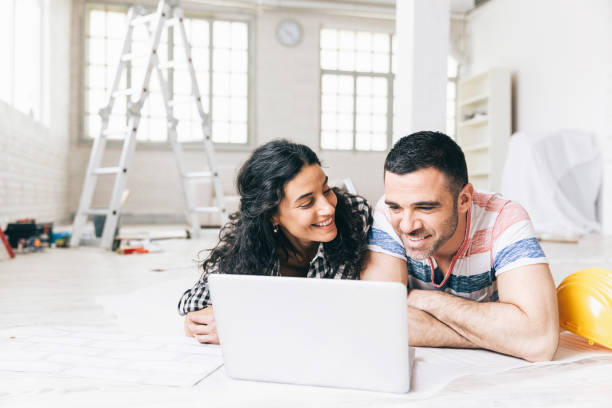 couple lying on the floor in a new apartment and using a laptop - renovation stock photos and pictures