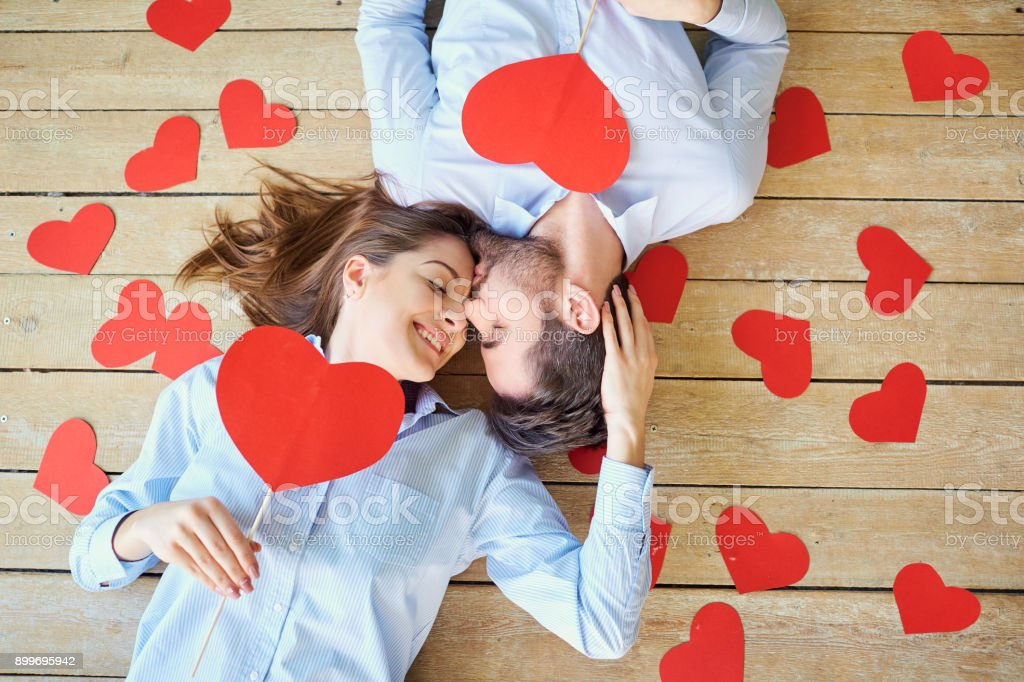 Couple lying on the wooden floor with hearts view from above stock photo