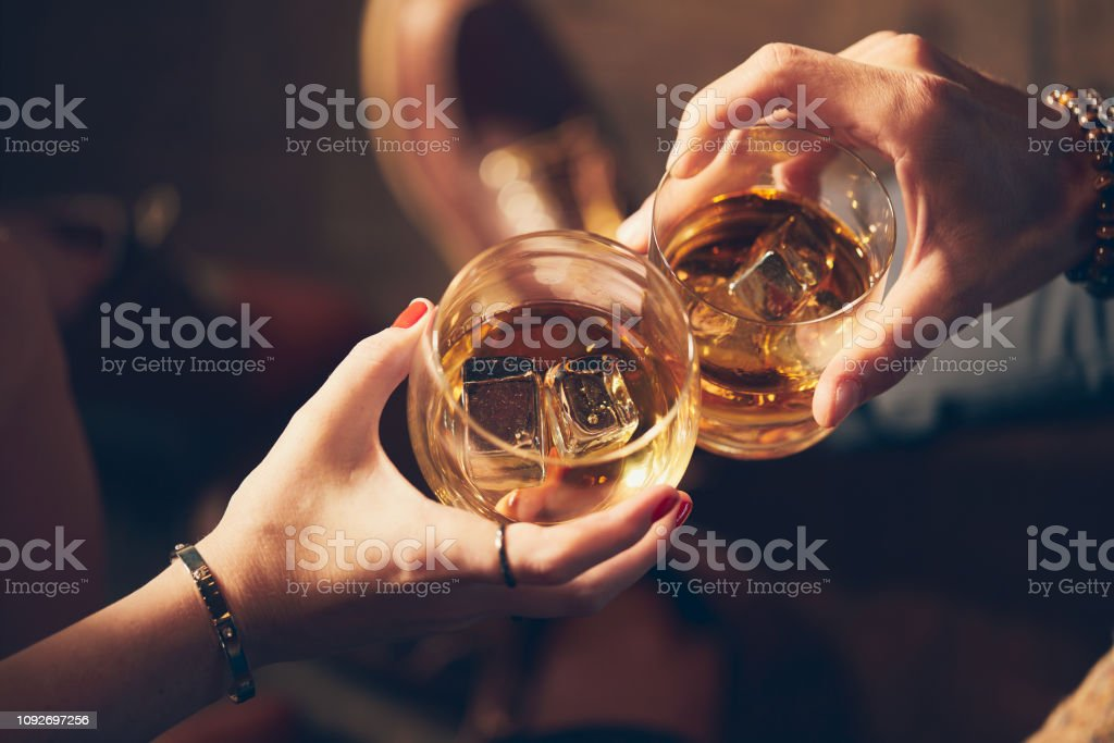 A couple makes a toast with two glasses of whiskey - Zbiór zdjęć royalty-free (Alkohol - napój)