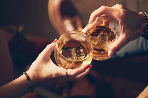 A Couple Makes A Toast With Two Glasses Of Whiskey - zdjęcia stockowe i więcej obrazów Alkohol - napój