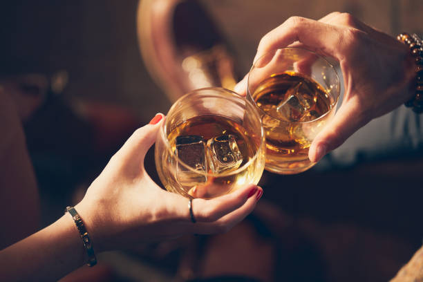 a couple makes a toast with two glasses of whiskey - bar zdjęcia i obrazy z banku zdjęć