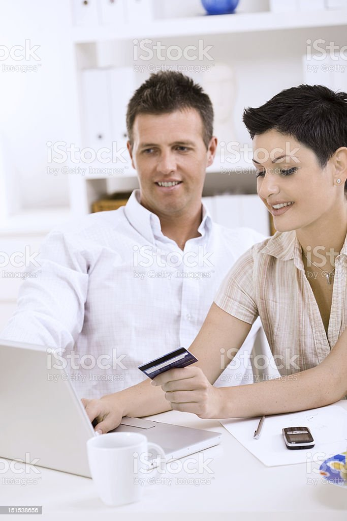 Couple making a purchase with a credit card on a laptop royalty-free stock photo