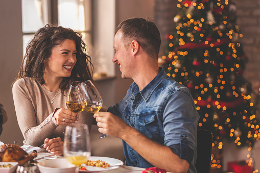 Beautiful couple in love having Christmas dinner with family, sitting at table and making a toast, raising glasses of wine