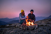 Couple in 30's making fire while camping outdoors, in an alpine wilderness near Whistler, BC, Canada.