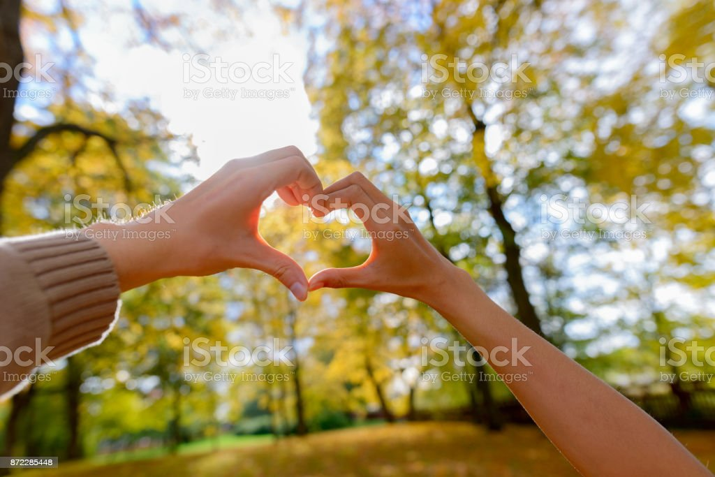 Couple making hand heart sign together towards the sky with scenic...