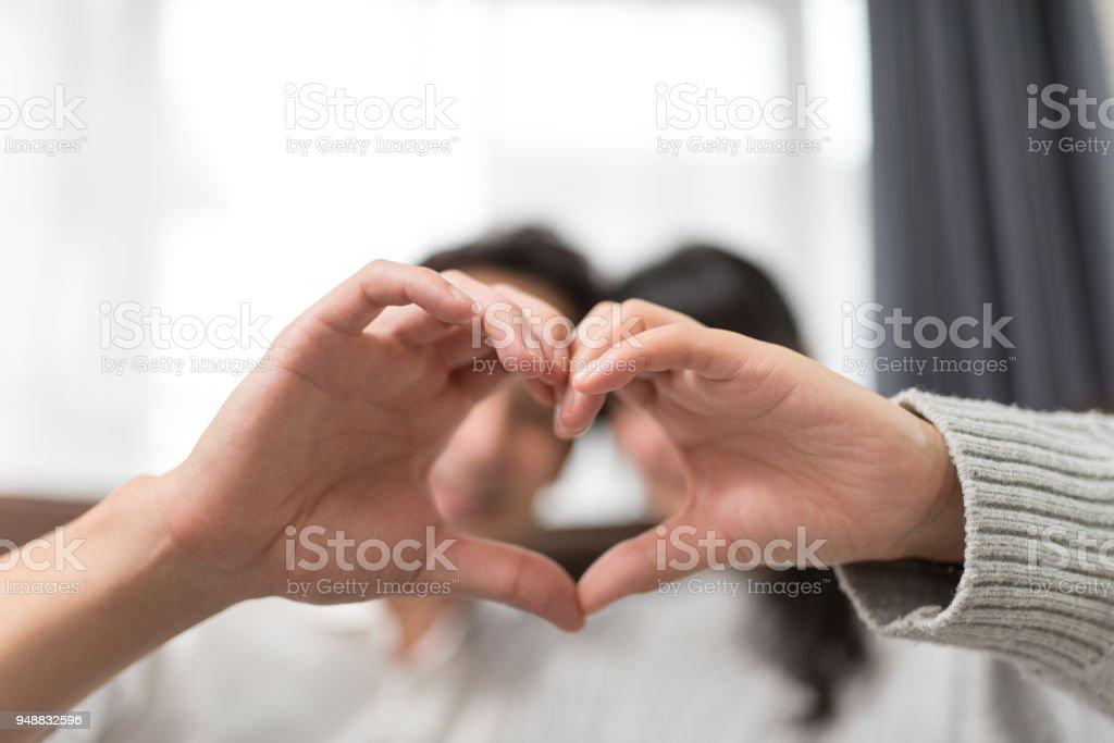 手でハートの形を作るカップル ストックフォト
