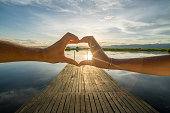Close up on couple's hands making heart shape frame on lake at sunrise, shot at Inle lake on wooden pier, Myanmar, Asia