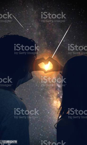 Photo of Couple making heart shape under the starry skies.