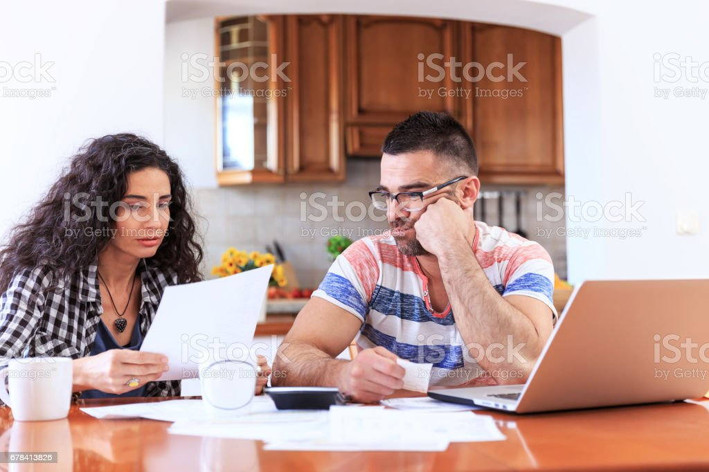Young couple sitting at home and making home finances. Both with...
