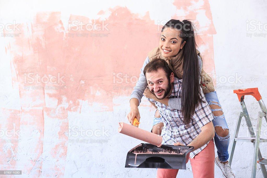 Couple making home improvement in piggyback stock photo